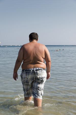 hombre con sobrepeso que entra en el mar