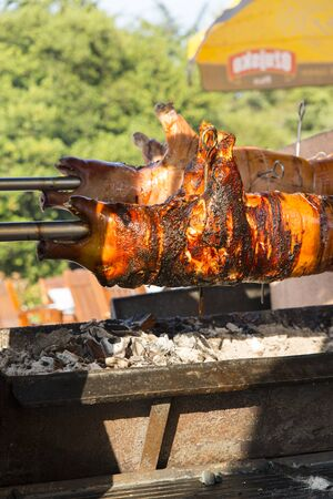 rotisserie with small pork cooked on the grill