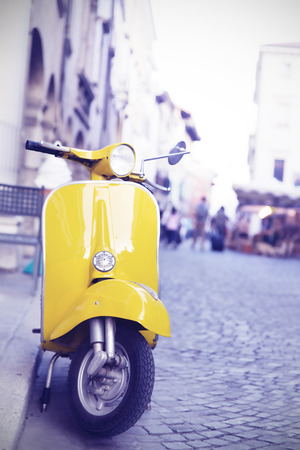 yellow Italian production motorcycle parked in the city
