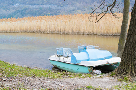 pedal: Pedal boats and abandoned on the shore of the lake Stock Photo