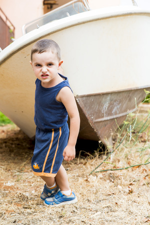 child playing in the garden pulling a boat