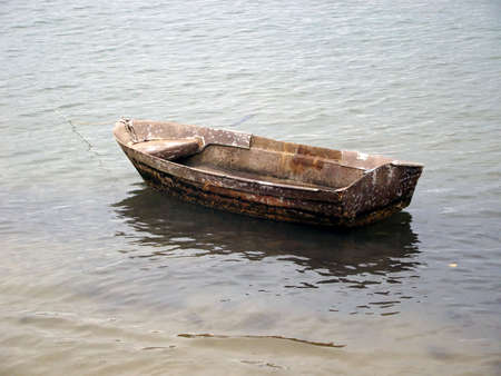 small wooden boat anchored on the beach