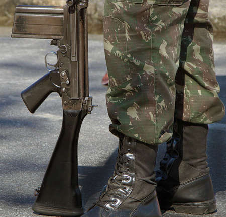 fatigues: legs of a brazilian camouflage soldier and his rifle