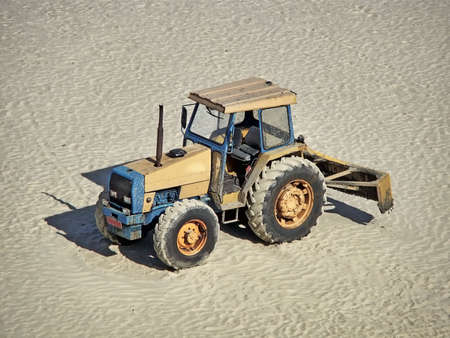 grader: a grader truck parked on the sand Stock Photo