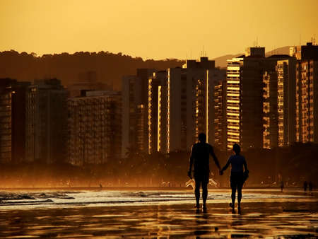 silhouette of couple holding hands walking on the beach photo