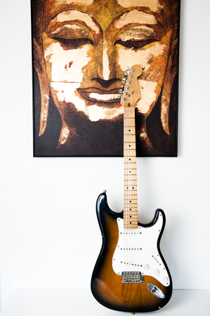 new age music: Face of Buddha together with electric guitar on white background Stock Photo