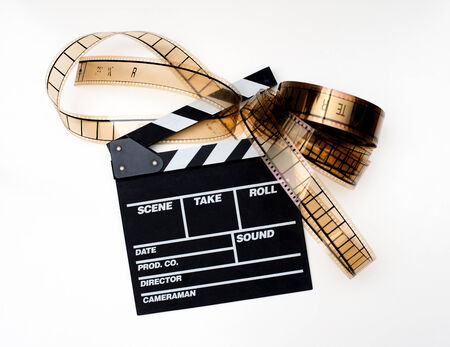 Movie clapperboard with film reel on white background photo