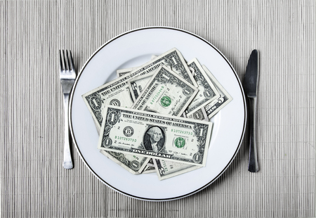 A plate with many dollars, a fork and a knife photo