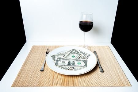 new economy: A table with white and black background, a plate with many dollars, fork, knife and glass of wine Stock Photo