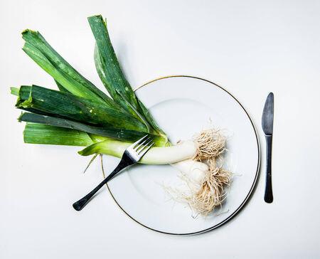 finer: Puerros frescos sin procesar en una placa blanca con el fondo blanco con un tenedor y un cuchillo