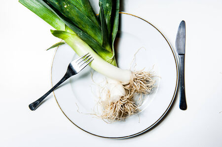 finer: Raw fresh leeks on a white plate with white background with a fork and a knife Stock Photo