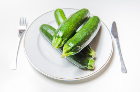 finer: Raw fresh zucchini on a white plate with white background with a fork and a knife