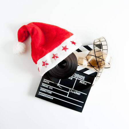 hollywood christmas: Santa Claus hat on a movie clapper board and a film reel isolated on white background Stock Photo