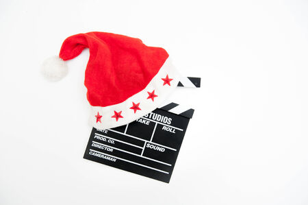 hollywood christmas: Santa Claus hat on a movie clapper board isolated on white background