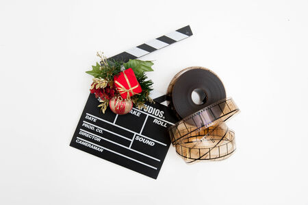 hollywood christmas: Film reel and clapper board with christmas decoration isolated on white background