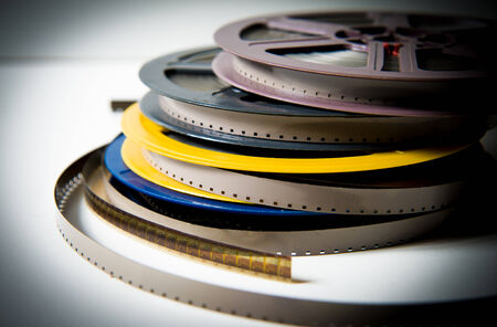 super 8: Pile of gray, blue, yellow and purple 8mm super 8 movie reels on white background, vintage look and color effect