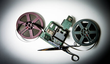 super 8: Couple of gray and purple 8mm super 8 movie reels, a splicer and scissors on white background, vintage look and color effect