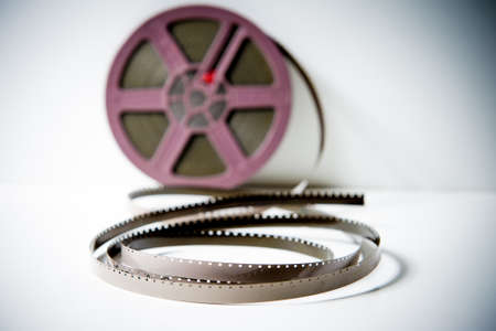 super 8: Detail of a 8mm super 8 film reel with purple detail out of focus on white background with purple reel out of focus on white background