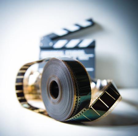 vintage look: 35 millimetri bobina film con batacchio fuori fuoco sullo sfondo, effetto di colore e look vintage