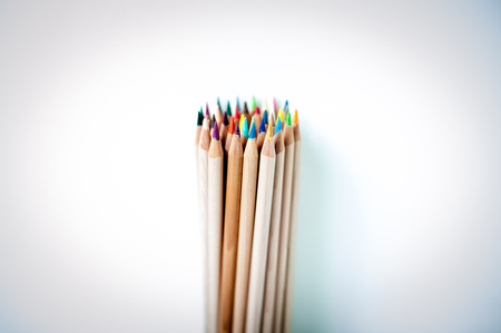 Bunch of pencil with wooden body and colored tips, vertical, pointing up, selected focus on the nearest row photo