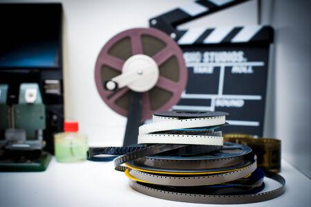 adentro y afuera: Un escritorio de edici�n de pel�culas de 8 mm de la vendimia con carretes y badajo de fondo fuera de foco, efecto del color de la vendimia Foto de archivo