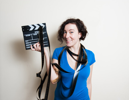 film editing: Young pretty woman with blue casual t-shirt and filmstrip around neck is smiling, holding a movie clapper on white background