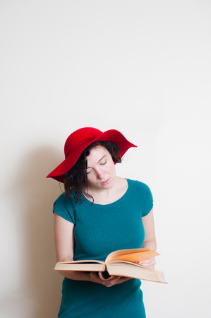 red hat: Young woman with red hat reading book on white background Stock Photo