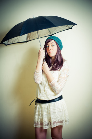 Young woman in 70s hippie style posing with umbrella vintage color effect