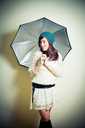 color effect: Young woman in 70s hippie style posing looking down with umbrella vintage color effect