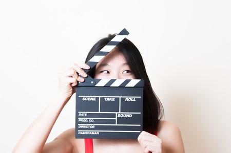 Jonge mooie Aziatische vrouw in een rode jurk close-up op zoek naar links met clapperboard op een witte achtergrond Stockfoto
