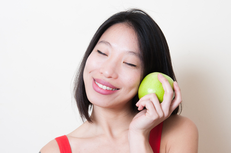 closing eyes: Young beautiful asian woman in red dress closeup smiling and closing eyes with green apple on her left hand near face on white background