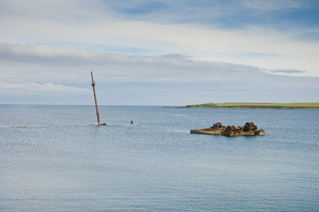 sunken boat: Old rusted sunken boat Orkney island, Scapa Flow, Scotland in cloudy day Stock Photo