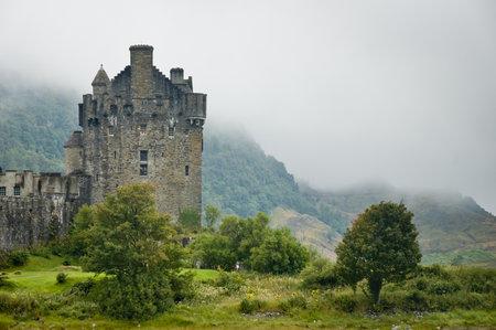 highlander: Vista del Castillo de Eileen Donan, Escocia en día nublado con luz dramática Editorial