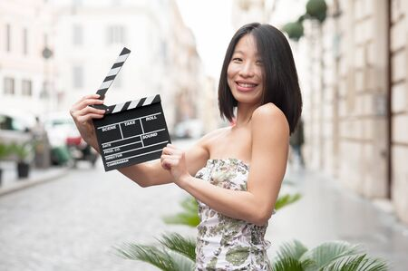 hot girl: Young asian woman smiling. showinmg  clapperboard on the road