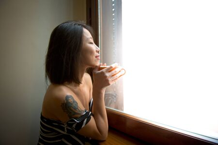 strong light: Beautiful smiling asian woman close eyes early morning alone feels positive with orange cup between hands. Strong light from the window