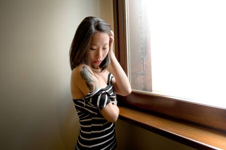strong light: Beautiful seductive young asian woman posing thoughtful, strong light comes from window