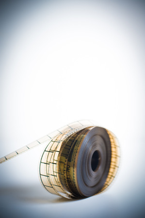 35mm: 35mm movie reel, unrolled with selective focus and vintage color look and feel, vertical frame and copyspace