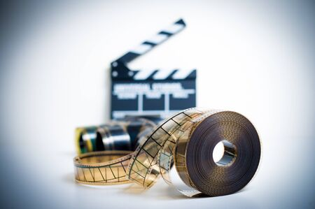 35mm: 35mm movie reel with out of focus clapper in background, color effect and vintage look
