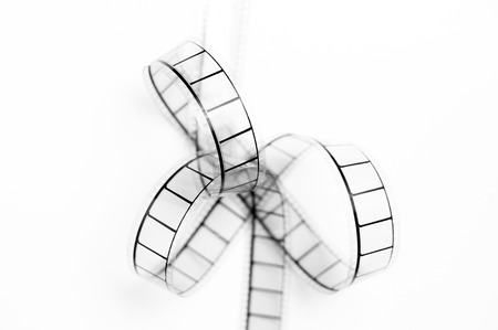 35mm: 35mm movie filmstrip bow closeup, black and white on white background Stock Photo