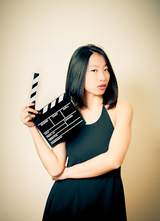 seductive look: Beautiful asian woman showing movie clapper board, seductive look and vintage colors effect