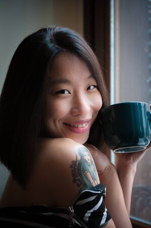 positive feeling: Asian cute woman smiles with green mug, looking at camera, positive feeling