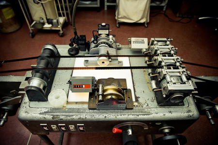 16mm: Audio video industrial film synchronizer for movie post production in old factory, vintage movie processing Stock Photo