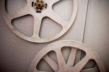 16mm: Movie reels part with filmstrip crossing on projector detail, 16 mm film format in vintage colors Stock Photo