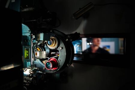 35 mm: 35 mm movie cinema projector machine in dark projectionist room with out of focus cinema screen in theater Stock Photo