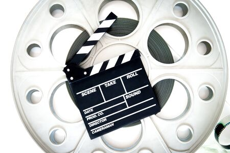 35 mm: Original old big movie reel for 35 mm cinema projector loaded with film, with clapper board on neutral background Stock Photo