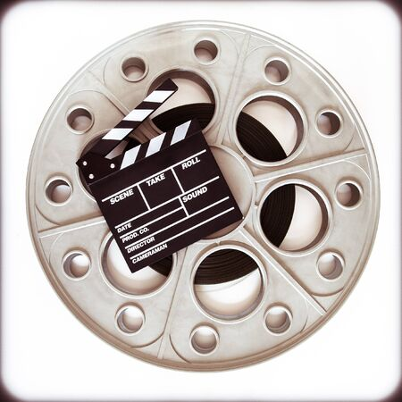 35 mm: Original old big movie reel for 35 mm cinema projector loaded with film, with clapper board on neutral background vintage color effect