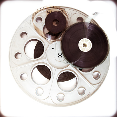 35mm: Original old big theater movie cinema 35mm loaded reel with film reels on neutral background and vintage color effect Stock Photo