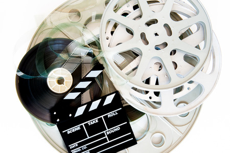 Stack of different movie film reels with clapper board on white background photo