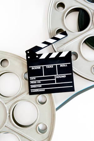 35 mm: Two movie reels for 35 mm film projector with clapper board and filmstrip on neutral background, vertical frame