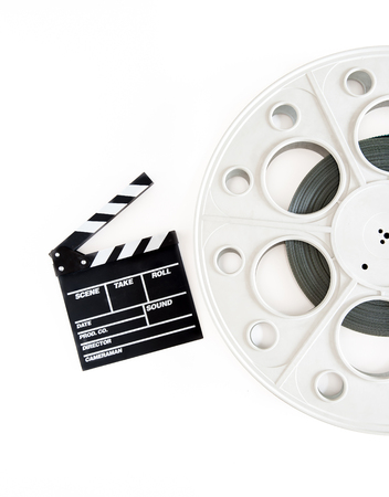 35 mm: Original vintage big movie reel for 35 mm cinema projector loaded with film, with clapper board on white background Stock Photo